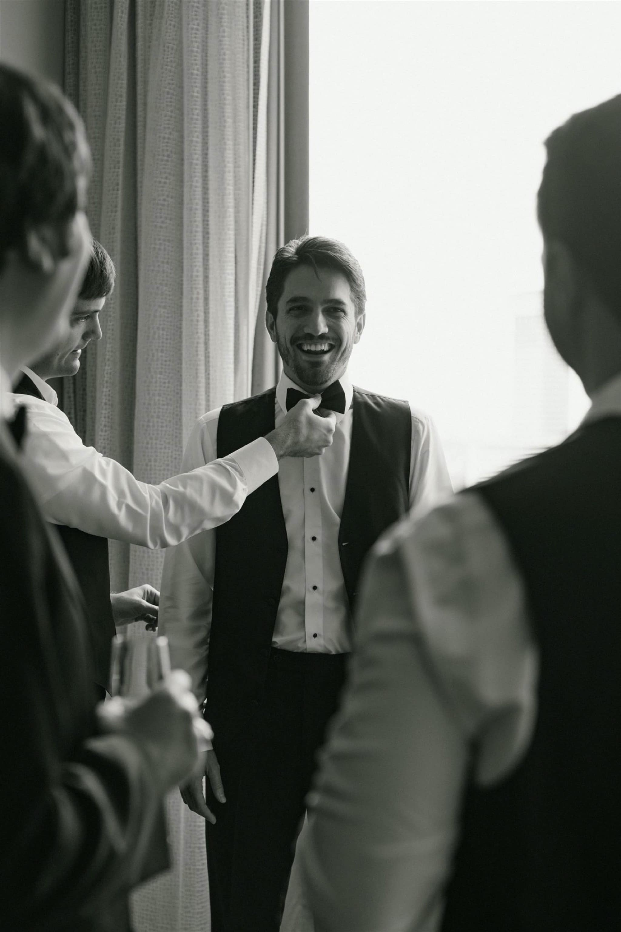 black & white groom getting ready
